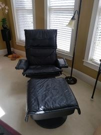 Black leather chair and ottoman; floor lamp