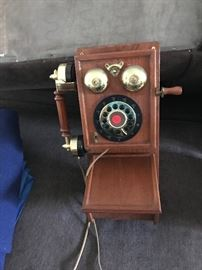 Button dial wall phone made to look like old fashion roatary phone with storage on bottom.