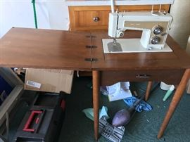 Old sears electric sewing  machine attached to sewing table with various accessories