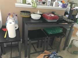 Long high top table with 4 backless stools. Various kitchen items and bakewear.