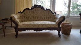 Professionally reupholstered antique loveseat with detailed wood carving.