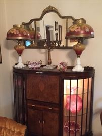This is a very fine Art Deco Drop-front Desk and Cabinet in very high style.  The desk uses the best richly-grained woods.  On its top  is a pair of 19th century oil lamps of wonderful glass, painted and mounted in gilt, signed by the painter. These are museum-quality pieces.