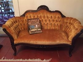 A fine rococo Love Seat from the 1850's (or perhaps, as has been suggested, a wide chair designed for one lady's hooped skirt).  It is unusual and of very high style. On the sofa is a boxed antique dressing set.