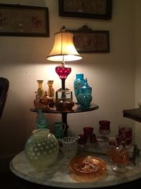 Another view of the Living Room with a striking Cranberry Glass oil lamp, electrified, with more art glass displayed on a marble-topped coffee table below it.  At the left is a stunning Felton lamp globe.