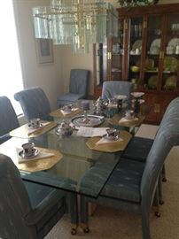 Contemporary polished travertine marble base and glass top dining table; 8 chairs.