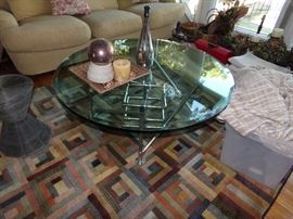 Very Thick Glass Top Table with a Chrome Pipe Understructure sitting on a nice Floor Rug