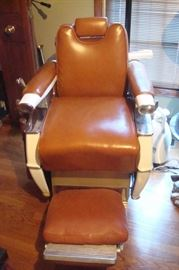 Antique barber chair with leather surfaces in excellent condition.