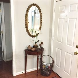 Small Demilune table, oval wall mirror, and decorative accessories