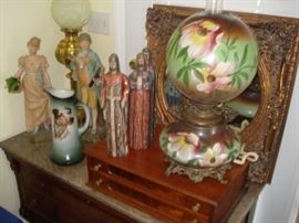 gold mirror,  porcelain figurines, wooden carved figurines, gone with wind table lamp, walnut marble top chest.