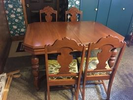 Antique table with 2 leaves for expansion. Five matching chairs.