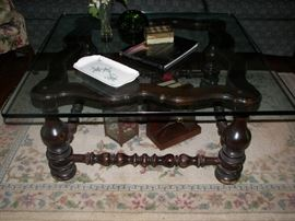 thick glass top coffee table with dark wood base and rug