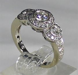 Ladies 14K White Gold And Diamond Ring 4.6 Grams, 3 Round Cut Diamonds W/Halo Of Round Diamonds Center Diamond is .50 Carat Grade SI H Two Outside Diamonds Are .25 Carat Each SI H 1.50 CTW Ring Size 6 3/4. LR2
