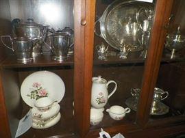 China Closet showing silverplate items along with a 12 piece china set