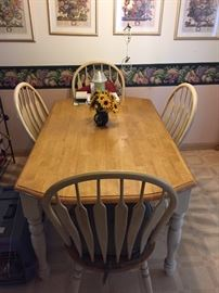 Farmhouse style table with four chairs.