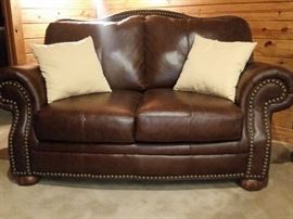 Leather love seat matches the sofa, chair, and ottoman