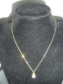 """""""SMALLS"""" Area:  A gold necklace is shown with a genuine pearl."""