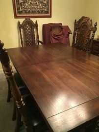 Elaborate solid pecan wood dining table with 10 chairs and 3 leaf inserts.
