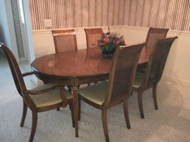 Vintage dining room table and 6 cane-back chairs (2 captain with arms and 4 without arms). Table has 2 leaves and pads.