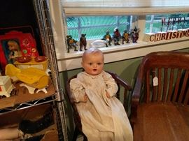 Baby doll from late 20s/early 30s. She has been well-loved, and shows it. She's still my favorite though. She is sitting in an antique high chair.