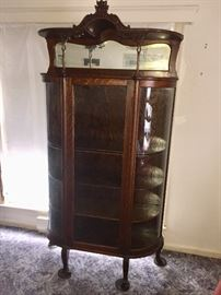 High Victorian china display cupboard. Quartersawn Tiger Oak with original dark finish. Ball and claw feet with mirror bonnet top. This piece can be purchased before sale. Call if interested.  This piece can be purchased before the sale. Call if interested.