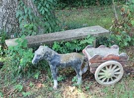 Donkey pulling a wagon and cement bench.