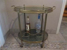1950's Mid-Century Modern bar/serving cart; brass with smoke glass; with wheels; top tray removeable; excellent condition.