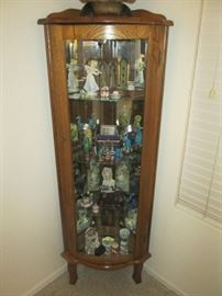 Lighted, oak curio cabinet, with key; curved glass; has 3 glass shelves; stands 6 ft tall x 3 ft wide; very good antique condition.