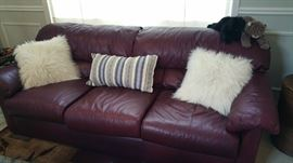 leather couch - handsome and unusual deep burgundy color...fun accent pillows and stuffed cats :)