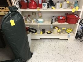 Green sack contains a tent with another sack containing poles, miscellaneous kitchen items
