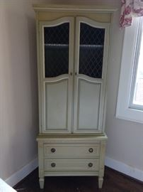 Sweet little MCM celery green, two-piece French Provincial wooden cabinet with metal grill doors above and two drawers below.