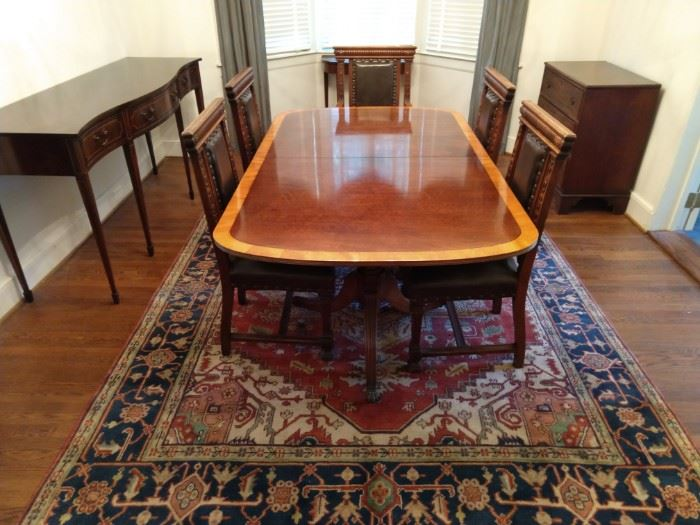 "Wonderful Henredon ""Ashton Court"" banded mahogany dining room table, with two 2' leaves (center), Federal style serpentine mahogany sideboard (left), antique English mahogany three-drawer chest (far right)."