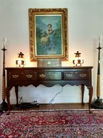 Vintage mahogany sofa table, with antique English writing box, vintage pair of unusual stained glass/cast iron table lamps, original oil on canvas of young mädchen mit schaf, flanked by a pair of vintage Kreiss torchieres.