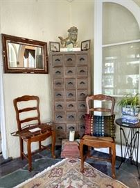 Artisan made wall mirror with birch bark and pinecones, 2 of a set of 6, Frenchy-style oak chairs with rush seats, one of a pair of golden foo dogs on travertine bases, one of a pair 3-legged accordion side tables, with zinc tops, one of a pair of those lovely 24-drawer storage chests.
