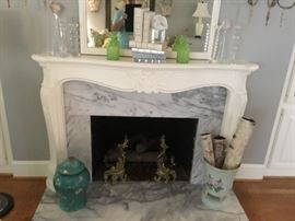 Brass andirons, lidded vase, wood pail, and white leather books on the mantle.