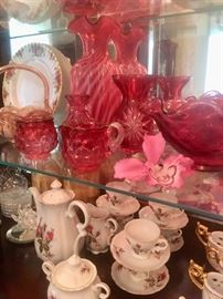 Many pieces of cranberry glass