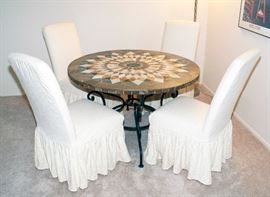 """Arhaus marble table top with cast iron legs with four covered chairs - 48"""" Diameter x 30"""" Height."""