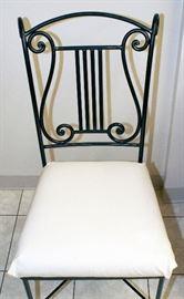 Arhaus cast iron chair with musical theme detail.