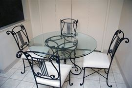 """Arhaus glass table with cast iron legs and four cast iron chairs with musical theme  - 48"""" Diameter x 29' Height."""