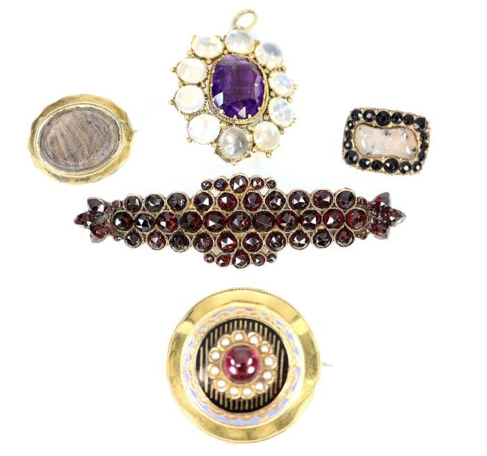 "A Group of Five 19th Century Brooches -  Including 1 jet and moss agate pin, engraved and dated 1817, 1 small mourning brooch, 1 amethyst and moonstone pendant/brooch, 1 Victorian garnet brooch, and 1 Late 18-Early 19th Century European gold brooch/locket with enamel decoration that is centered by a garnet cabochon and twelve seed pearls, stamped with two faint markings at the clasp.  Wear to each piece, the gold brooch/locket has some misshapen portions around the edge, the Victorian garnet brooch lacks the pin.  Up to 2 3/4"" long.  Totaling 32.5 grams."