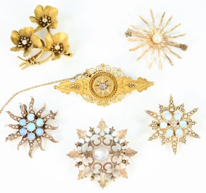 "A Group of Six Brooches - Including 3 14 kt gold, opal, and pearl brooches, 1 14 kt yellow gold Victorian brooch with small diamond enhancement at the center, 1 brooch with three flowers all centered by small diamonds, and 1 medallion form brooch with moonstone center.  All but the last two mentioned brooches are marked.  Wear to each, some losses to the seed pearls, wear to the medal of the medallion form brooch.  Up to 1 5/8"" long.  Totaling 20.9 grams."
