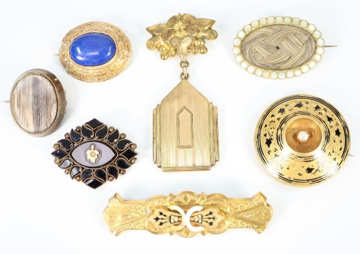 "Seven 19th Century Brooches -  Including 2 Mourning brooches featuring encapsulated hair, 1 Jet Mourning brooch that is centered by a gold-tone leaf with seed pearl accent, 1 gold-plated brooch with suspended locket, 1 round and 1 rectangular gold-tone brooch with black enamel, and 1 gold brooch with oval lapis stone.  All are unmarked.  Wear to each, the black enamel is slightly worn and the setting of the lapis brooch is slightly misshapen.  Up to 2 1/2"" long.  Totaling 56.4 grams."
