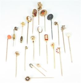 "Twenty-One 19th Century Stick Pins - Consisting of one marked ""Sterling""  sliver pin, one marker ""10 k"" gold, along with nineteen unmarked pins decorated with various real and synthetic gemstones and enhancements. Wear noted overall, with some bent or misshapen pins, and one with horseshoe lacking some decoration. Up to 3"" long. Totaling 39.4 grams."