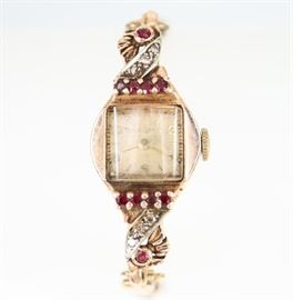 "A Vintage Bulova Rose Gold, Diamond, & Ruby Ladies Wrist Watch -  14 kt Rose Gold watch with 6 diamond and 8 ruby enhancements about the face, on a double snake chain style bracelet.  Stamped ""14KT"".  Scratches noted, scuffs/nicks/flakes noted to the crystal.  Not running when cataloged.  Totaling 15.7 grams."
