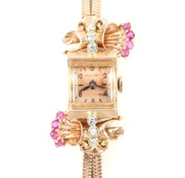 "A 1930's Ollendorff  14 k Rose 14 k Gold, Diamond, & Ruby Ladies Wrist Watch -  Beautiful rose gold watch with 6 diamond and 8 ruby enhancements about the face, on a double snake chain style bracelet.  No apparent markings.  Some wear/scratches evident, minor nicks to the crystal, some discoloration to the face.  Not running when cataloged.  6 1/2"" long.  Totaling 25.1 grams."