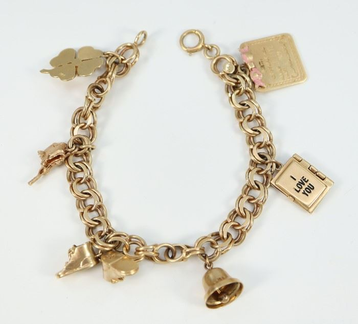 "A 14 kt Yellow Gold Charm Bracelet -  Bracelet hung with 6 charms including a Birth Certificate, a Marriage License, a bell, baby booties, a swimsuit, and a shamrock with pearl accent.  Bracelet and charms are all stamped ""14K"".  Some wear/scratches noted.  7 1/4"" long.  Totaling 30.8 grams."