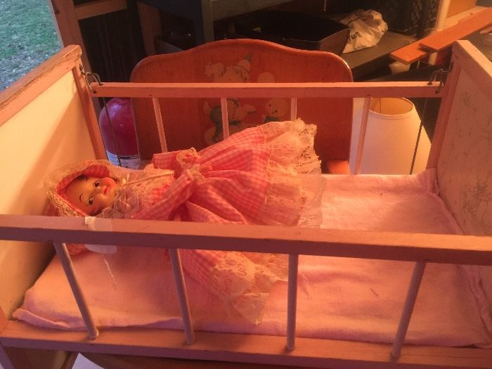 Wooden doll crib with one side that actually comes down with metal bar simulates a real crib it is pink & cream in color