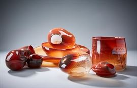 Lot #40 Dale Chihuly (b. 1941). Nine amber glass baskets of varying sizes and shapes. Largest signed and dated 1980 along the base. Provenance: Private collection, Chicago, Illinois. Biography: Dale Chihuly first encountered glass art as an interior design student at the University of Washington. Immediately fascinated, he went on to study glass at the University of Wisconsin, which was the first university in the United States to teach glassblowing. From there, he went on to the Rhode Island School of Design, where he continued to learn about glass and eventually ended up teaching. His education continued with a Fulbright Fellowship to go to the famous glassblowing studios of Venice. After his time in Italy, he returned to his home state of Washington to found his own glass school, the Pilchuck Glass School, with Ann and John Hauberg, influential supporters of the arts in Seattle. At this school, his art style and process truly flourished. In particular, Chihuly first fostered the col