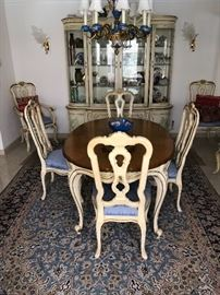 One of a kind handpainted French provincial dining room set. Eight chairs (table shown without leaf), four panel door, four shelf china cabinet with four bottom doors. Intricately  hand painted with a delicate floral and botanical design along apron, legs, backs, doors.