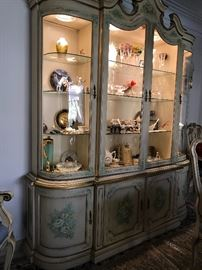 Lighted, handpainted and gilt trimmed china cabinet.