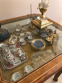 Limoges and Bavarian porcelain children's tea service shown within figural gilt and glass horizontal curio table.